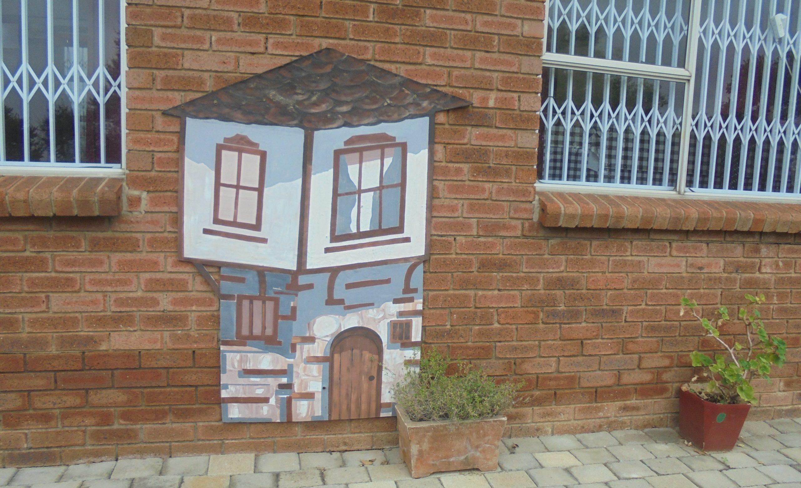 Композиция с рисунка на традиционна българска къща и мушкато на стената на Българския културен център (Дом на българите) в Мидранд, Йоханесбург